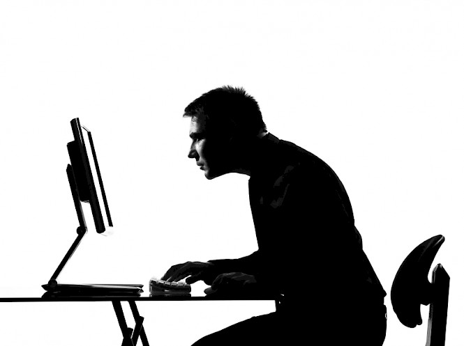 Man staring intently at a computer screen