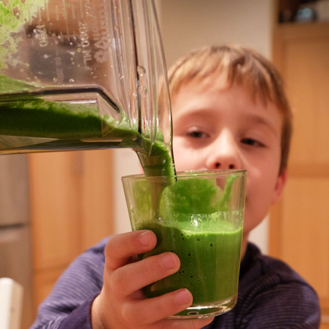 Child holding a green eye-healthy smoothie